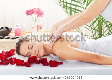 Massaging. Brunette getting a back massage in the spa salon - stock photo