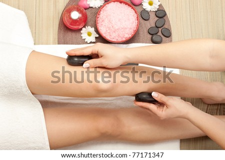 massaging of the human legs with hot mineral stone - stock photo