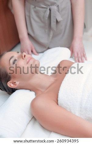 Massaging stress away. Closeup of young shirtless woman lying on front while massage therapist standing by the massage table