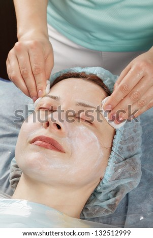 Massagist removing massage cream from caucasian woman face
