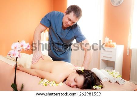 Masseur doing massage beautiful girl - stock photo