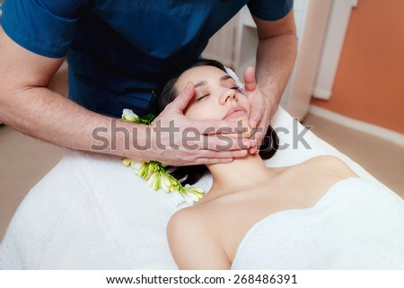 masseur doing massage of the face of a beautiful girl in a beauty salon. spa treatments.   - stock photo