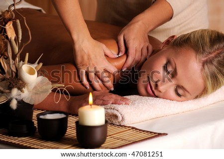 Masseur doing massage on female shoulder in the beauty salon - stock photo