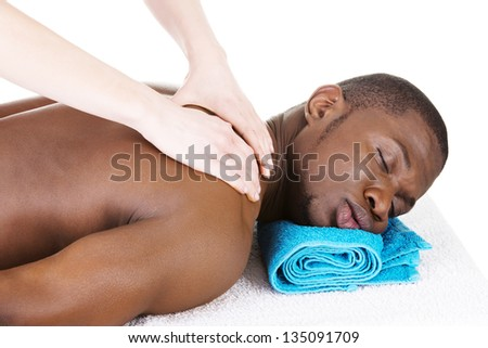 Masseur doing massage on man body in the spa salon. - stock photo