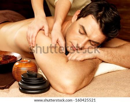 Masseur doing massage on man body in the spa salon. Beauty treatment concept. - stock photo