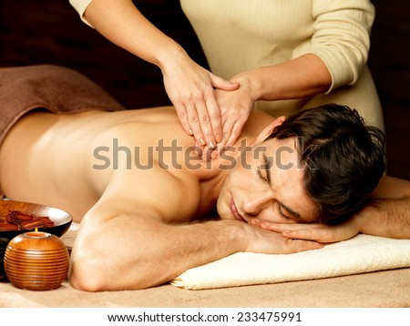 Masseur doing massage on man body in the spa salon. Beauty treatment concept.