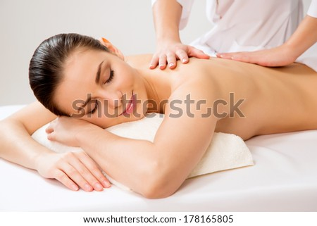 Masseur doing massage on the back of woman in the spa salon. Beauty treatment concept. - stock photo