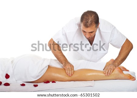 Masseur giving legs  massage to a woman at spa salon - stock photo