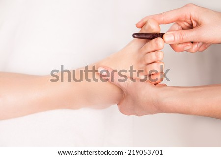 masseur makes thai foot massage young woman - stock photo