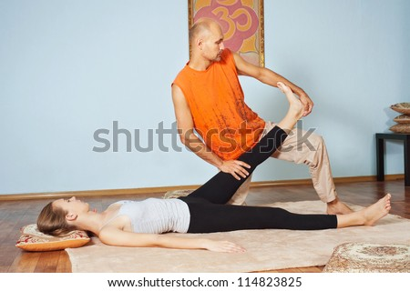 Masseur makes Thai massage girl - stock photo