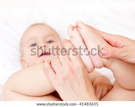 Masseur massaging little baby's feet, shallow focus - stock photo