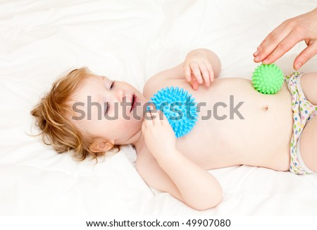 Masseur massaging little girl with rubber device, shallow focus - stock photo