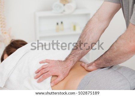 Masseur massaging the back of a woman in a room - stock photo