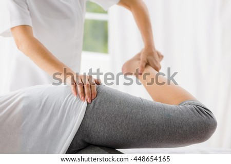 Masseur stretching woman at spa