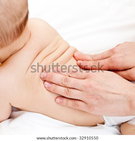 Masseuse massaging little baby girl, shallow focus - stock photo