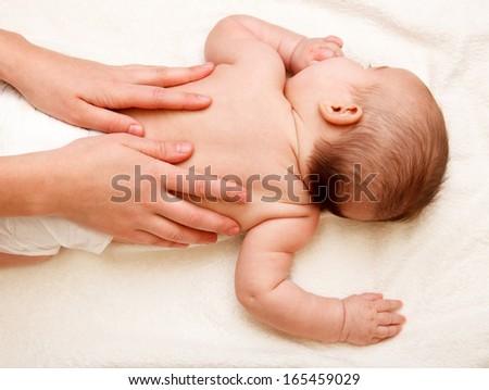 Masseuse massaging 5 months infant - stock photo