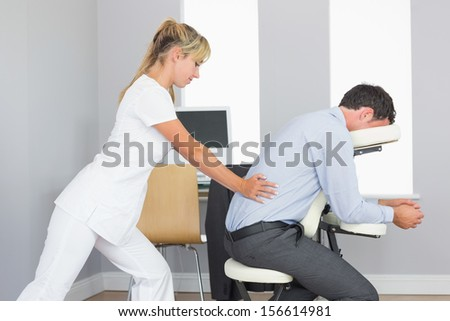 Masseuse treating clients lower back in massage chair in bright room - stock photo