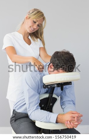 Masseuse treating clients neck in massage chair in bright room - stock photo