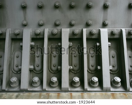 Massive bolts and supports holding the base of a bridge.