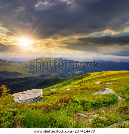 Massive boulders among wild plants on the hillside in high mountains at sunset - stock photo