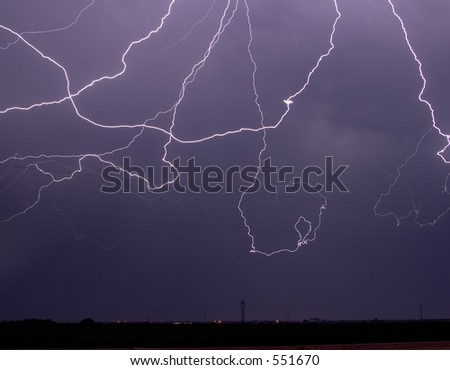 Massive cloud-to-cloud lightning event over power lines - stock photo