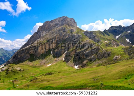 Massive Colac summit in Dolomites with blue sky and clouds in the background. - stock photo