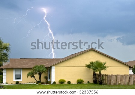 Massive daytime lightning strike near homes during afternoon storm - stock photo