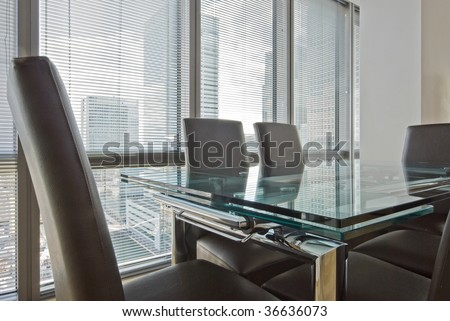 massive glass dining table with seating for six - stock photo