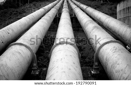 Massive hydro electric pipelines converge up a hill - stock photo