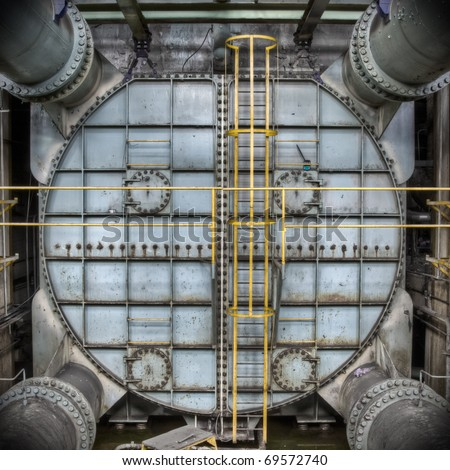 Massive metal construction at an abandoned power plant. Looks like some sort of pressure tank. - stock photo