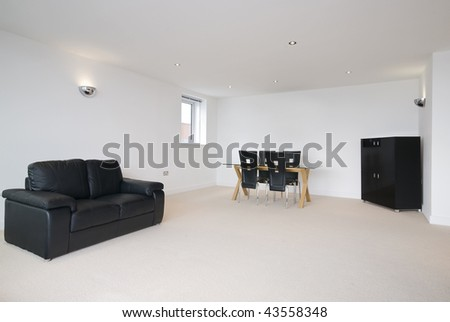 massive modern living room with black leather sofa and dining area - stock photo