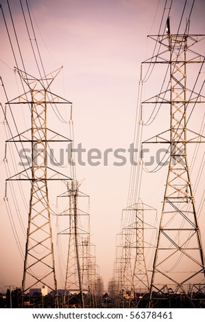 Massive power lines stretch into the distance - stock photo