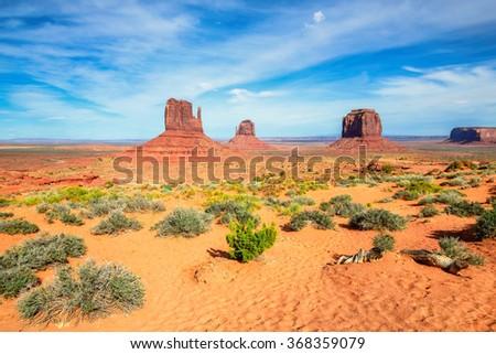 Massive sandstone pillars soar above iconic Monument Valley - stock photo