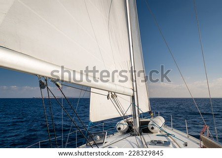 Mast and hoisted sails of sailing boat, going to the horizon. - stock photo