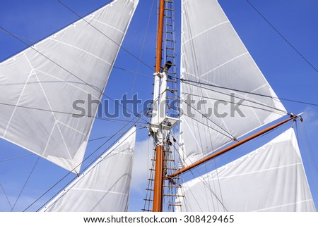Mast and white sails of sailing boat against blue sky - stock photo