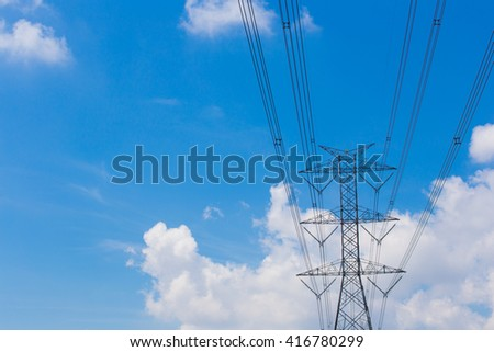 Mast electrical power line against cloud and blue sky.