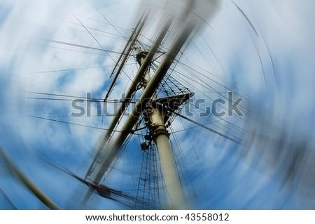 Mast of a sailfish on blue sky. - stock photo