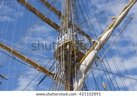 Mast of the sailing boat, blue sky in the background.