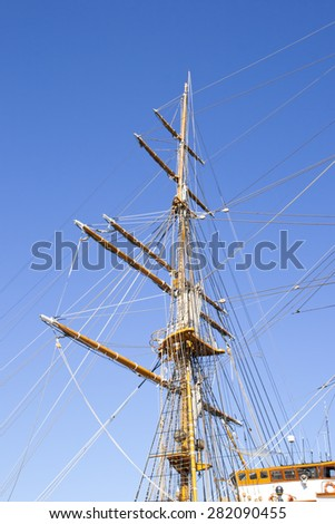 Mast sailing ship against a blue sky background - stock photo