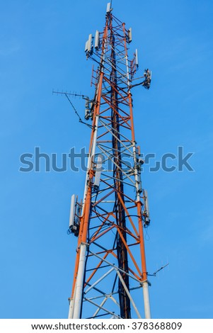 Mast with communication antennas on blue sky background - stock photo
