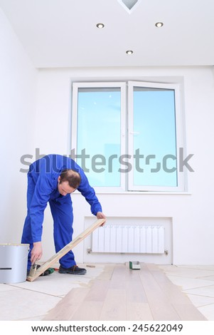 Master applies glue to floorboard with spatula in white room - stock photo