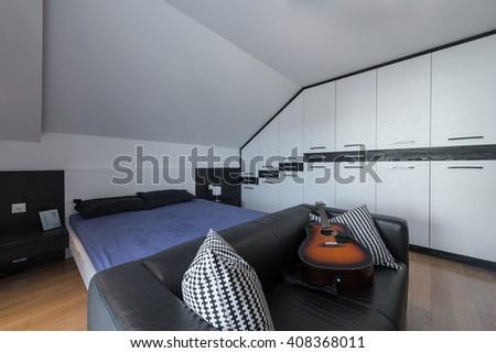 Master bedroom and dresser in attic interior - stock photo