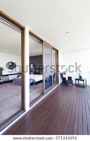 Master bedroom and large glass sliding doors to balcony in luxury Australian home - stock photo