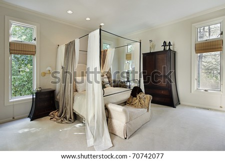 Master bedroom in luxury home with curtains around bed - stock photo