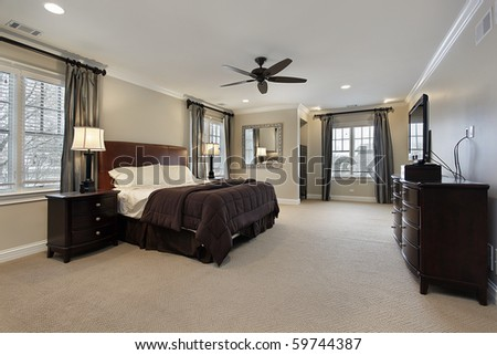 Master bedroom in luxury home with dark wood furniture - stock photo
