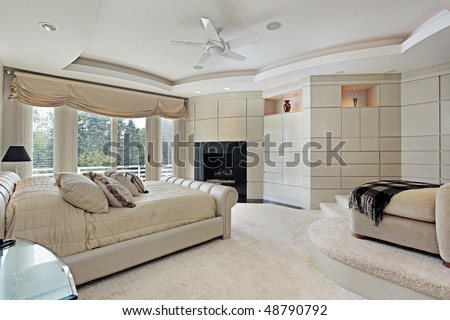 Master bedroom in luxury home with elevated sitting area - stock photo