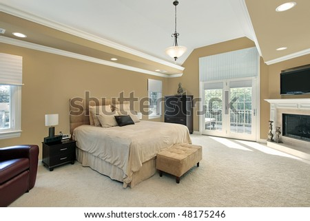 Master bedroom in luxury home with fireplace - stock photo