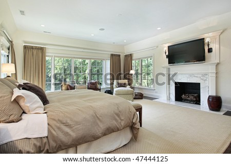 Master bedroom in luxury home with marble fireplace - stock photo