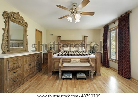 Master bedroom in luxury home with oak wood furniture - stock photo