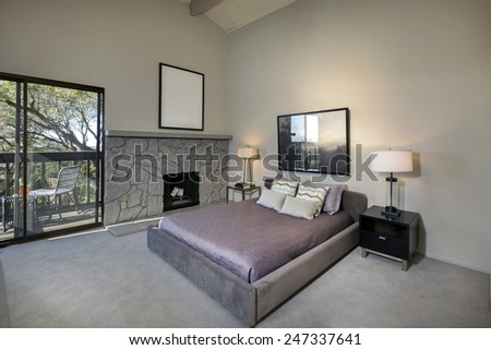 Master bedroom in luxury home with purple bed cover. - stock photo